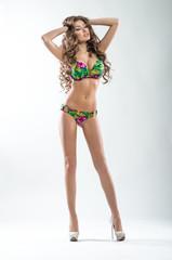 Slim tanned sexy woman in swimwear in studio