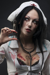 Dead nurse holding syringe with blood
