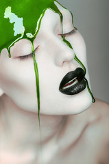 Woman with green gel pouring on face