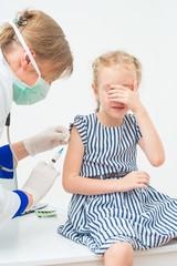 Female doctor doing vaccine to little girl.