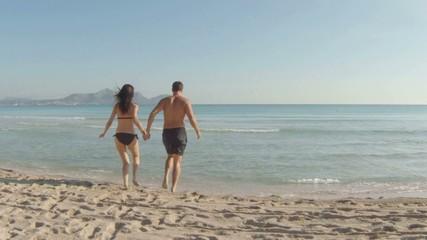 young couple having fun at the beach. majorca, spain.