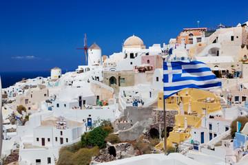 Oia town on Santorini island, Greece. Waving Greek flag