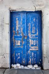 Grunge old blue door in Oia town, Santorini, Greece