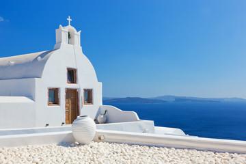 Oia town on Santorini island, Greece. White church and vase.