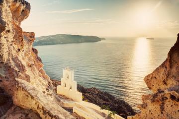 Cliff, volcanic rocks and old chapel on Santorini island, Greece