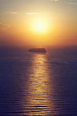 A lonely island, rock on the sea at sunset