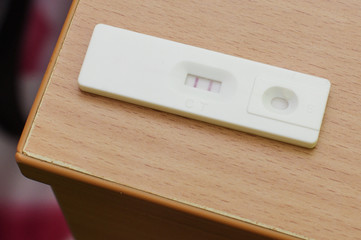 Positive pregnancy test on the wooden table