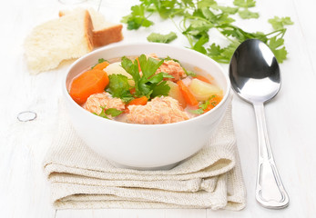 Fish soup with salmon in bowl on white wooden table