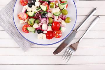 Greek salad served in plate on napkin on wooden background