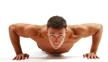 Handsome young muscular sportsman execute exercise isolated