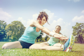 Two young girls stetching before a jogging