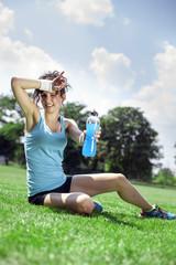 Tired woman runner taking a rest after run