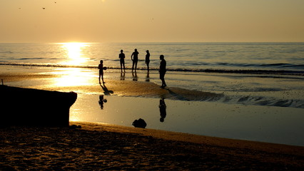 People silhouette on the beach ,at the sunrise