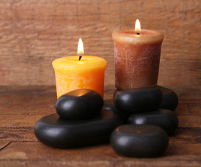 Spa stones with candles on wooden background