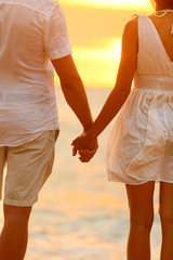 Romantic couple holding hands on beach sunset