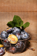 Ripe sweet plums in old metal basket, on wooden table