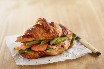 Butter croissant with avocado and salmon