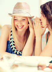 girls gossiping in cafe on the beach