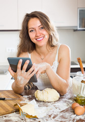 Housewife cooking with tablet at home