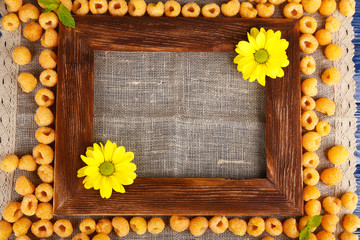 Yellow raspberries, wooden photo frame and wildflowers