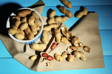 Peanuts in bowl on color wooden background