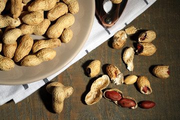 Peanuts on plate, on wooden background