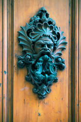Ancient door knocker on a wooden door in Florence
