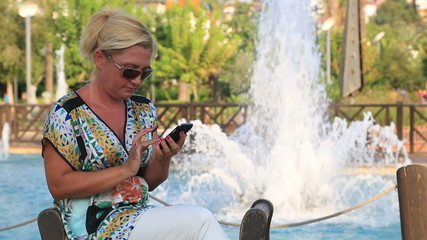 Business woman using smart phone near the park fountain