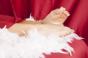 woman feet on boa red sheet