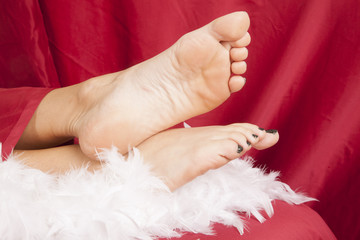 woman feet on white boa and red sheet