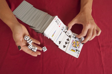 woman hands flipping playing cards holding dice