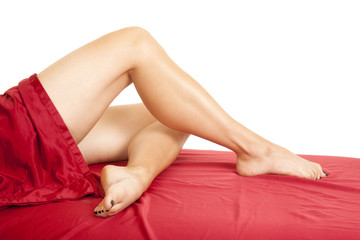 woman legs in red sheet on bent under other