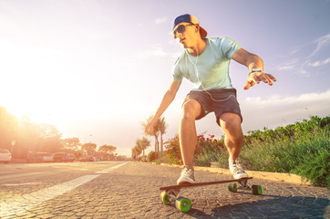 Man on longboard skate in action at sunset