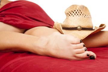 woman legs red sheet tan western hat on calf
