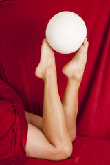 woman legs under red sheet hold up ball