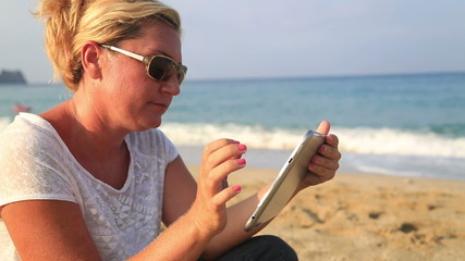 Woman using digital tablet on the beach and smiling to a camera