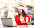 smiling woman in santa hat with gift and laptop