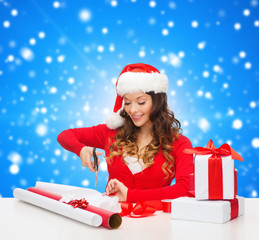 smiling woman in santa helper hat packing gift box
