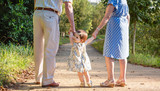 Baby granddaughter walking with her grandparents outdoors