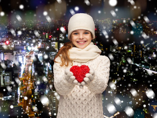 dreaming girl in winter clothes with red heart