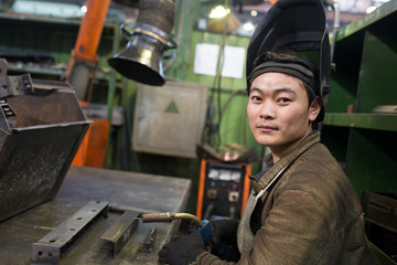 Positive asian welder worker at workplace