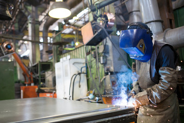 Worker welding metal at factory workshop with flying sparks