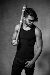 sexy fashion man model with a baseball bat posing dramatic