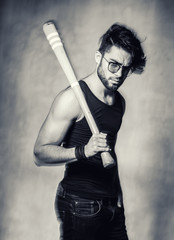 sexy fashion man model with a baseball bat looking angry