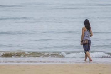 Mujer en la playa mirando al mar