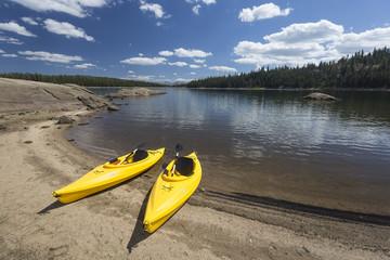 Pair of Yellow Kayaks on Beautiful Mountain Lake Shore.