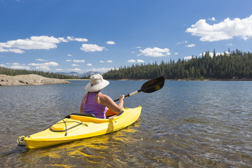 Woman Kayaking on Beautiful Mountain Lake.