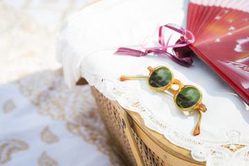 Sunglasses, Chinese Fan and Picnic Basket on Blanket