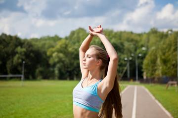 Красивая стройная девушка занимается спортом на природе