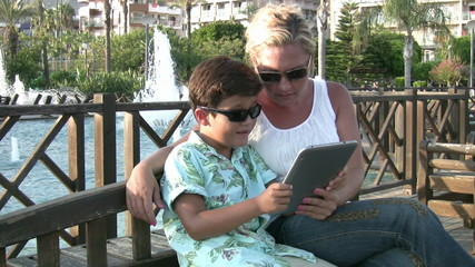 Mother and son using digital tablet outdoor